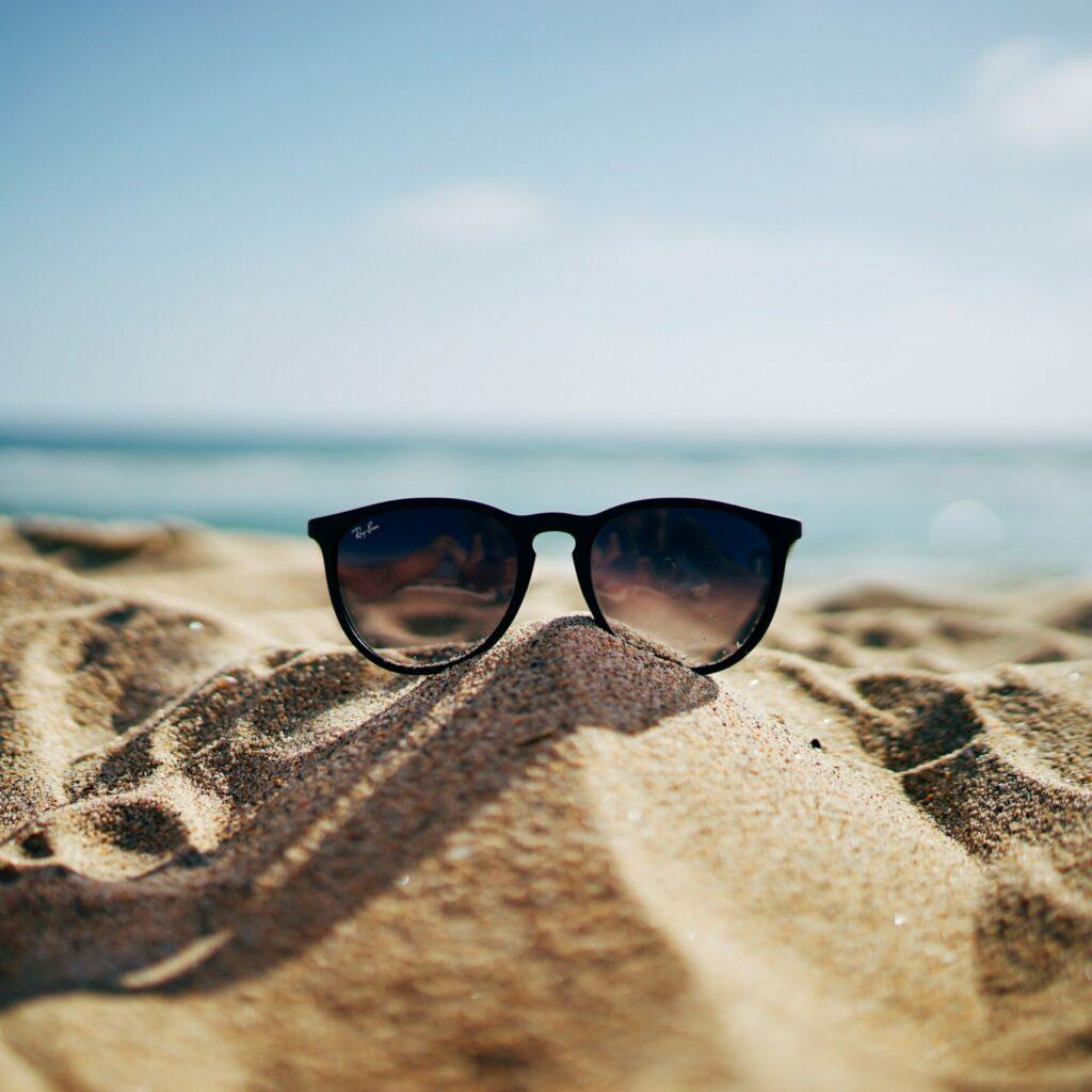 black Ray-Ban Wayfarer sunglasses on beach sand